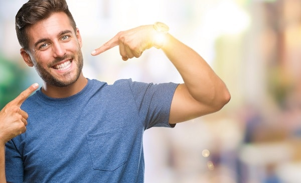 Man pointing to his smile to show off adult braces results